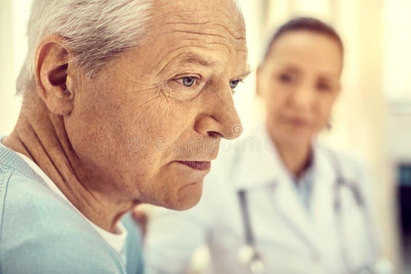 Feche acima do retrato do cavalheiro aposentado infeliz no hospital foto de stock