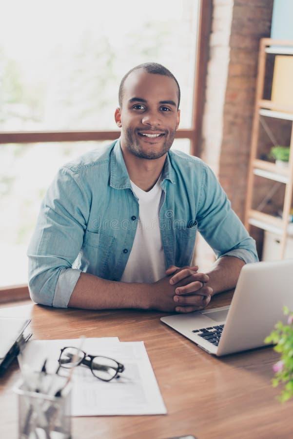 Feche acima do retrato colhido do indivíduo preto alegre está olhando na câmera, sentando-se em seu lugar de trabalho no escritór imagens de stock