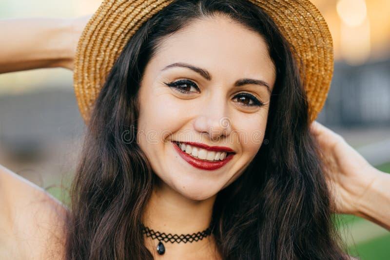 Feche acima do retrato da fêmea bonito com o cabelo escuro, os olhos encantadores e o chapéu vestindo do verão da palha do sorris foto de stock