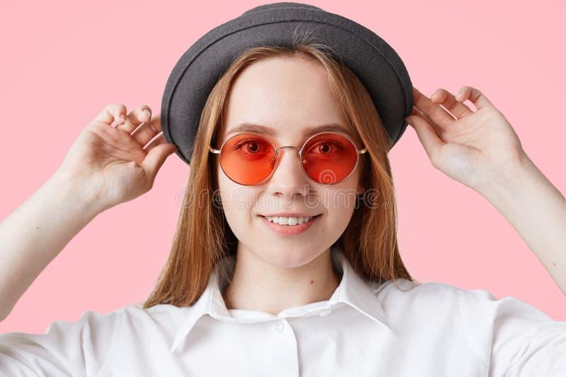 Feche acima do retrato da fêmea deleitada bonita com sorriso agradável, vista óculos de sol à moda e o chapéu negro vermelhos, is foto de stock