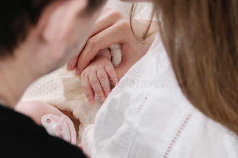 Feche acima do retrato da família das mãos bonitos pequenas do bebê no h do pai fotografia de stock