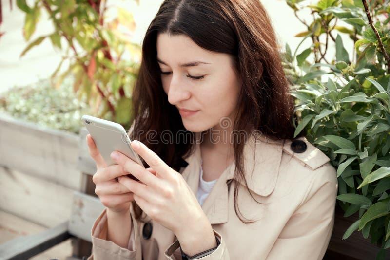 Feche acima do retrato da jovem mulher que guarda o smartphone em suas mãos fotografia de stock
