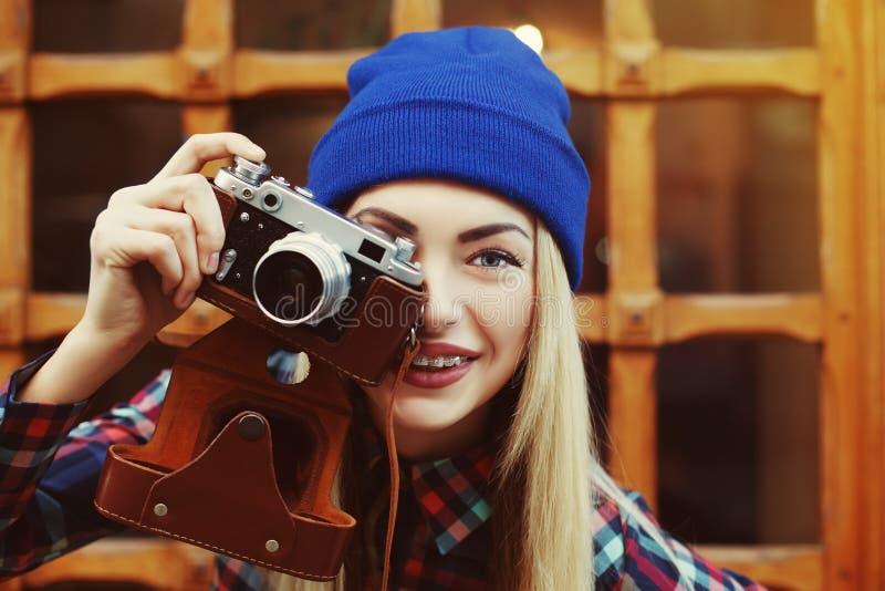 Feche acima do retrato da menina de sorriso feliz à moda do moderno nas cintas com photocamera do vintage Looking modelo na câmer imagem de stock