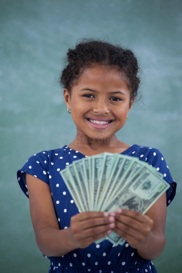 Feche acima do retrato da menina de sorriso que mostra a moeda de papel imagem de stock