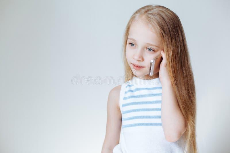 Feche acima do retrato da menina europeia loura pequena bonito na roupa ocasional que fala no telefone celular e no sorriso branc imagens de stock