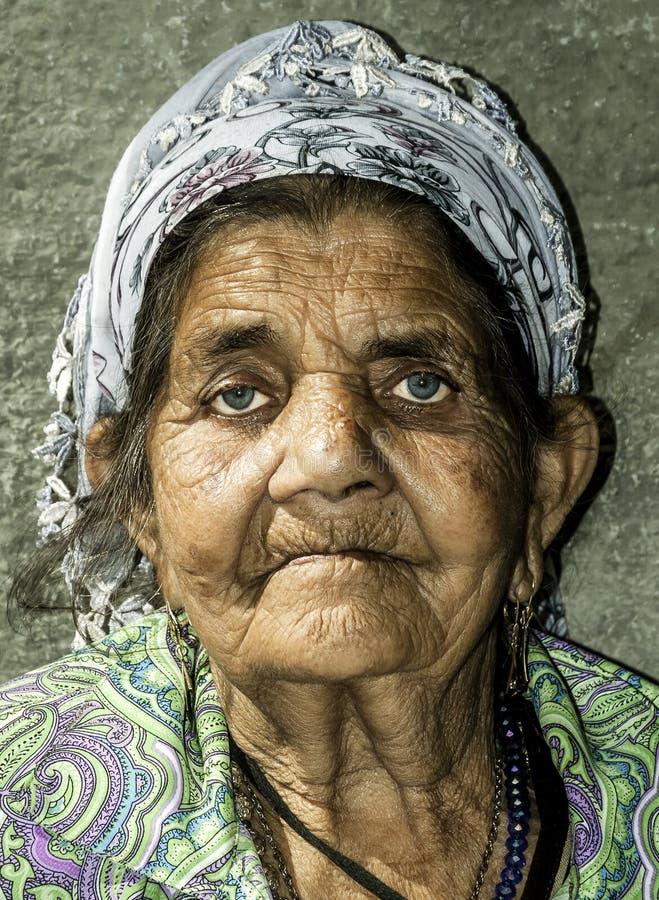 Feche acima do retrato da mulher aciganada desabrigada idosa do mendigo com pele enrugada da cara que implora pelo dinheiro na ru foto de stock