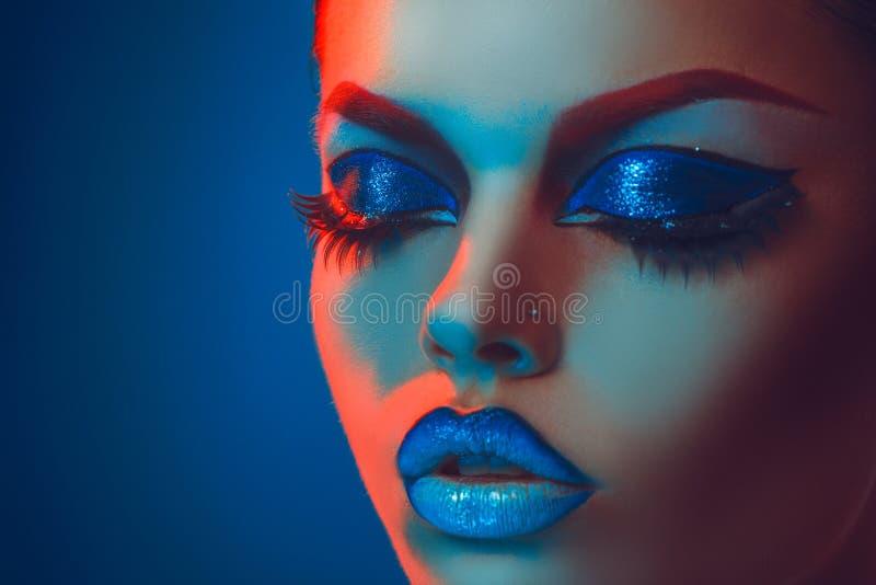 Feche acima do retrato da mulher adulta com os olhos fechados em vermelho e em azul imagens de stock