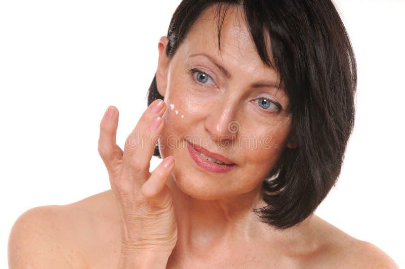 Feche acima do retrato da mulher consideravelmente superior que usa o creme de cara imagens de stock royalty free