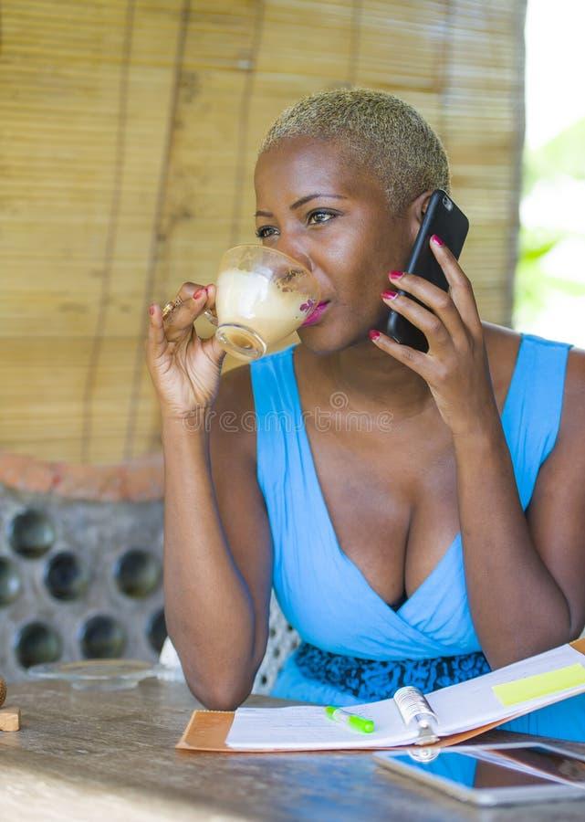 Feche acima do retrato da mulher de negócio afro-americana preta bonita e feliz nova no cabelo à moda na moda que fala no telefon fotos de stock royalty free