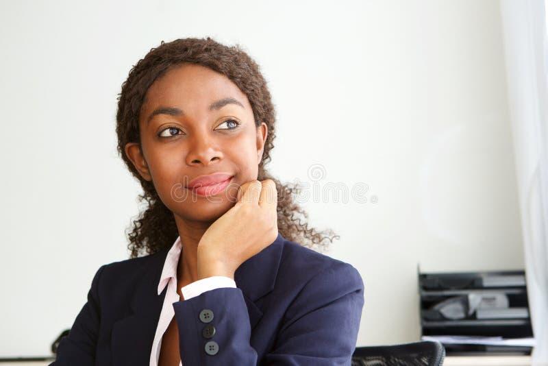 Feche acima do retrato da mulher de negócios africana nova que senta-se em sua mesa que olham ausente e no pensamento foto de stock royalty free
