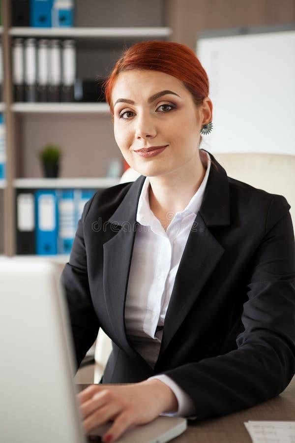 Feche acima do retrato da mulher de negócios de sorriso com um portátil na frente dela que olha a câmera imagem de stock royalty free