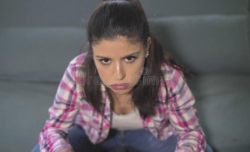 Feche acima do retrato da mulher latino-americano atrativa e triste nova que senta em casa o sofá que olha forçado e preocupado e foto de stock