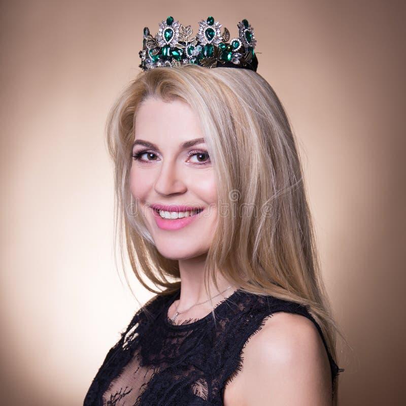 Feche acima do retrato da mulher loura bonita nova com coroa sobre imagem de stock