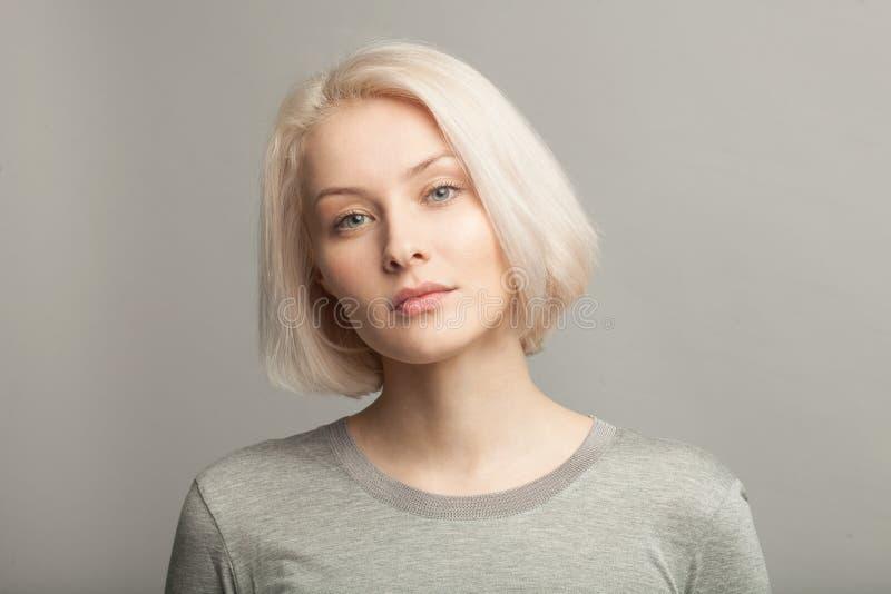 Feche acima do retrato da mulher loura bonita nova no backgr cinzento foto de stock