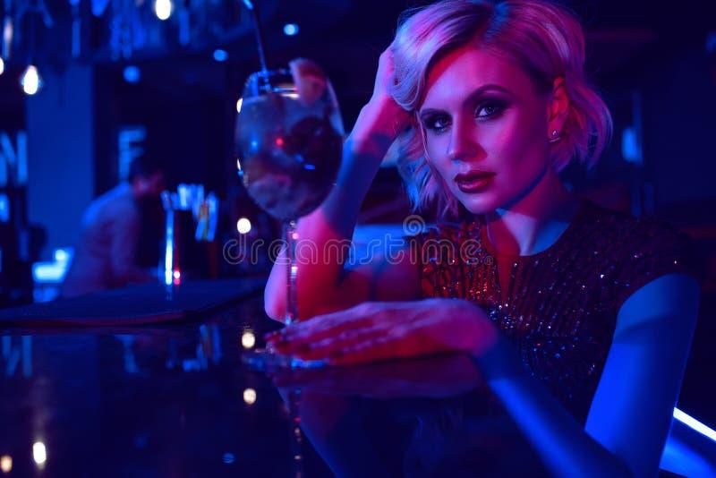 Feche acima do retrato da mulher loura glam bonita que senta-se na barra no clube noturno em luzes de néon coloridas que bebe o c imagens de stock