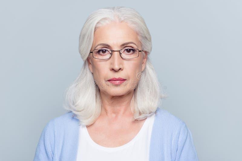 Feche acima do retrato da mulher séria, envelhecida, encantador nos vidros ov fotos de stock