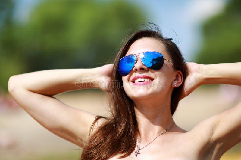 Feche acima do retrato da mulher 'sexy' bonita à moda nos vidros e com cabelo molhado em uma praia ensolarada com água azul imagens de stock royalty free