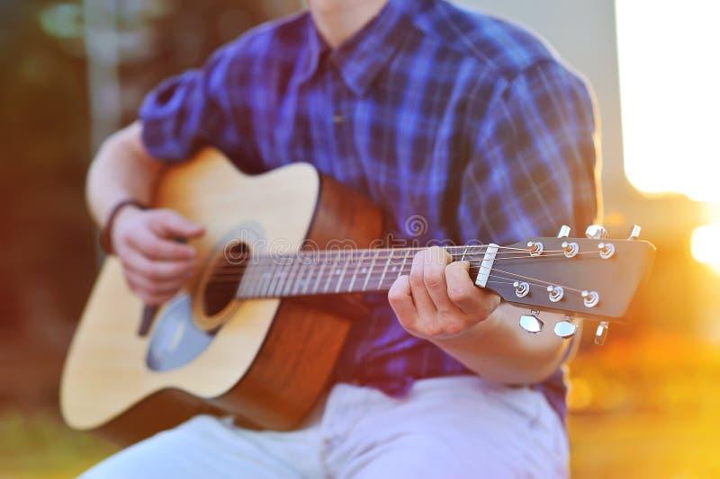 Feche acima do retrato das mãos masculinas que jogam a guitarra acústica imagem de stock