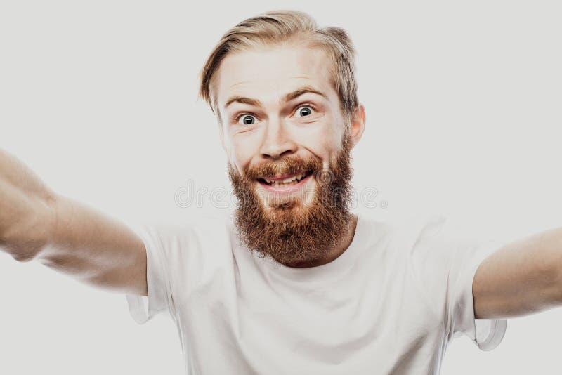 Feche acima do retrato de um homem farpado alegre que toma o selfie sobre o fundo branco imagem de stock royalty free