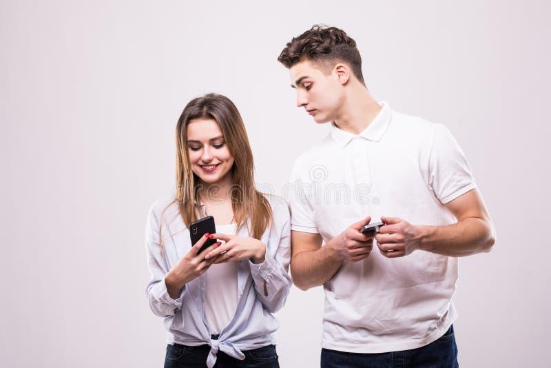 Feche acima do retrato de um par de sorriso inter-racial usando telefones celulares no fundo cinzento Olhar do homem em telefones fotos de stock