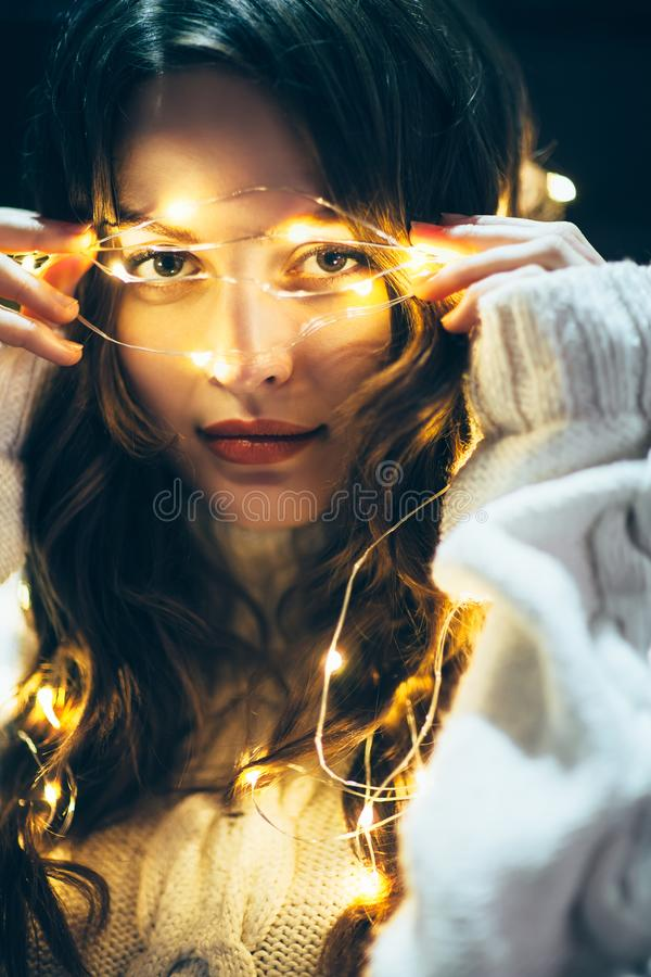 Feche acima do retrato de uma jovem mulher bonita com ligh do Natal imagem de stock royalty free