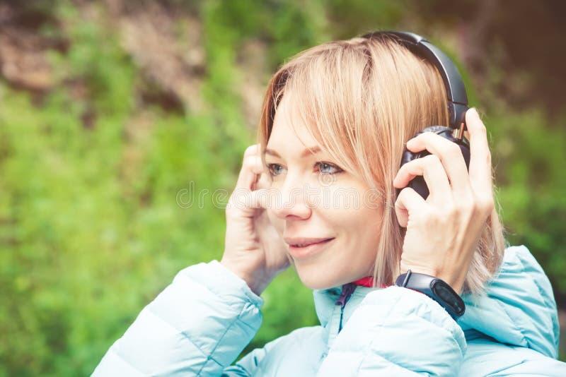 Feche acima do retrato de uma jovem mulher bonita que guarda os fones de ouvido que escutam a música fora na música alegre da flo fotografia de stock