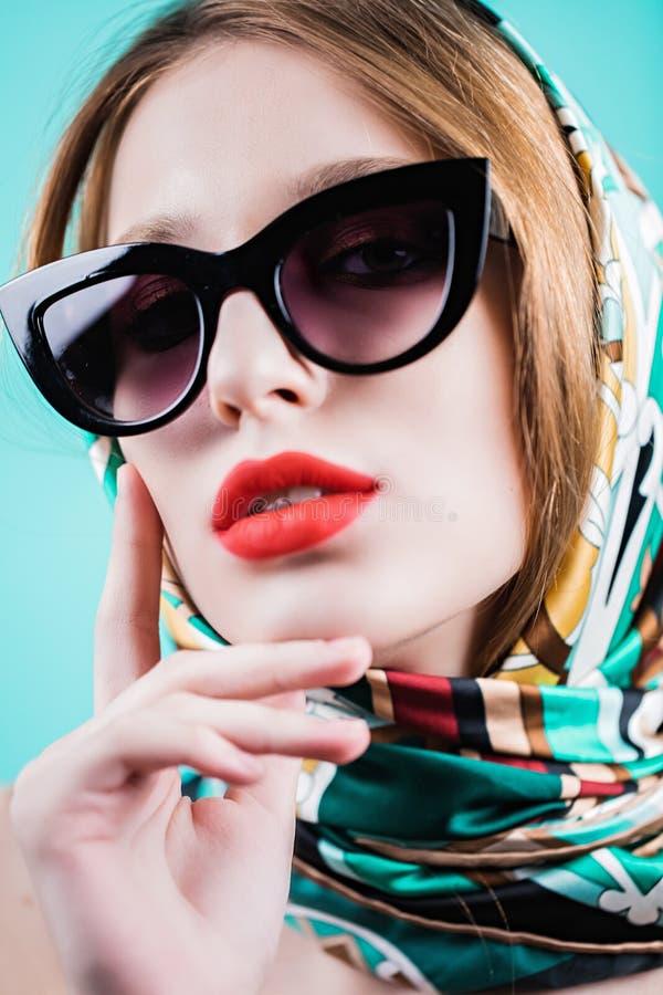 Feche acima do retrato de uma menina bonita nos óculos de sol e no lenço no estúdio foto de stock royalty free