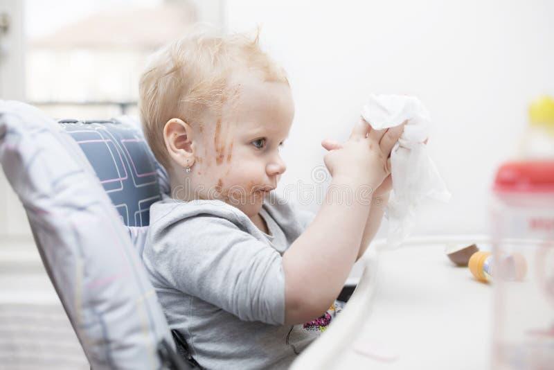 Feche acima do retrato de uma menina idosa de dois anos que comem a barra de chocolate e da cara coberta no chocolate foto de stock
