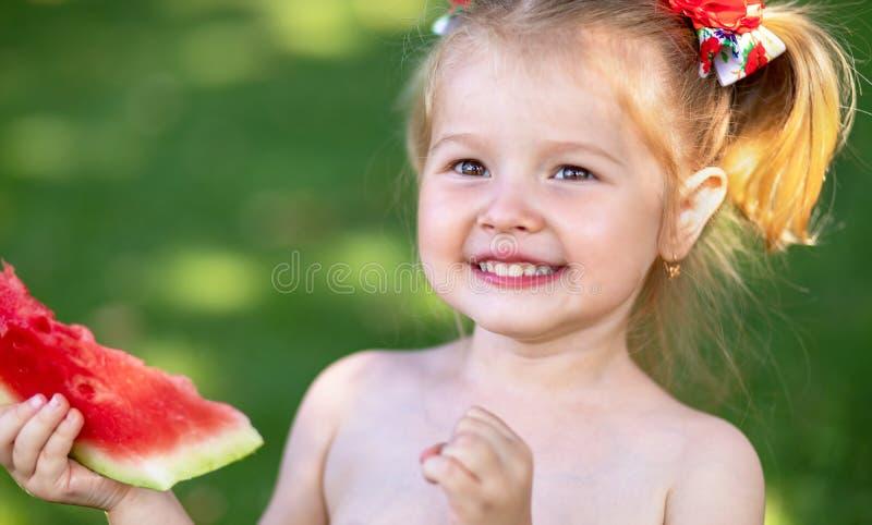 Feche acima do retrato de uma menina loura nova com melancia, fotografia de stock royalty free