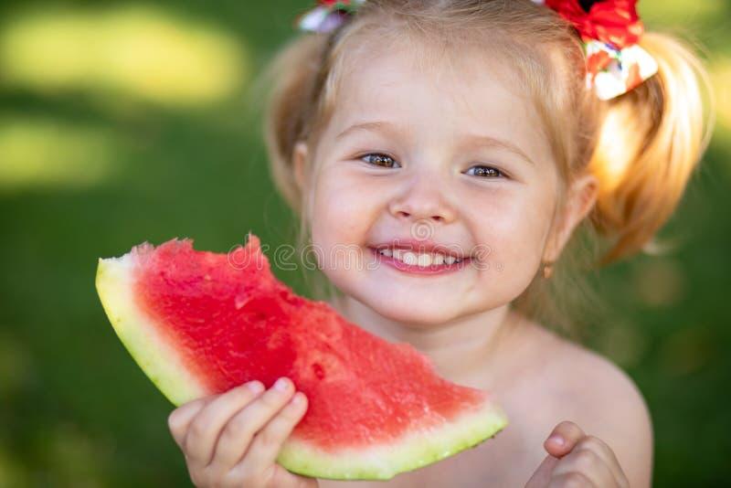 Feche acima do retrato de uma menina loura nova com melancia, petisco saudável exterior do verão para crianças foto de stock