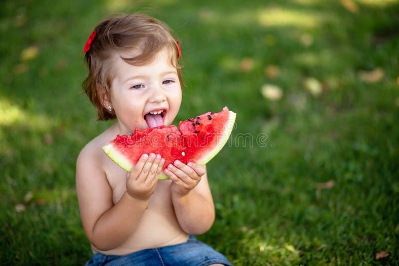 Feche acima do retrato de uma menina nova com melancia, petisco saudável exterior do verão para crianças fotografia de stock