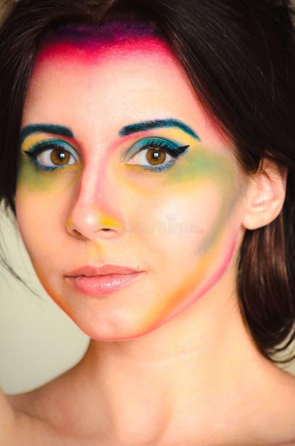 Feche acima do retrato de uma mulher bonita nova com composição colorida no fundo claro foto de stock