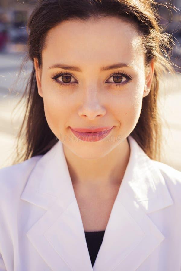 Feche acima do retrato de uma mulher de negócio moreno bonita no terno branco imagem de stock royalty free