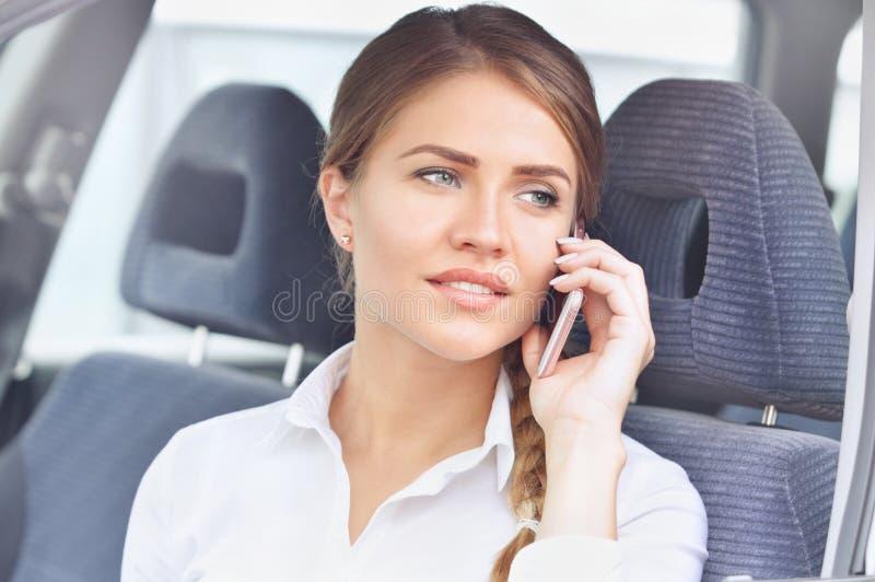 Feche acima do retrato de uma mulher de negócios que fala no telefone celular no carro fotografia de stock