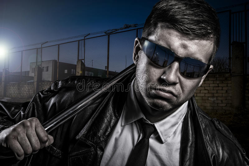 Feche acima do retrato do homem perigoso secreto à moda com bastão de aço imagem de stock