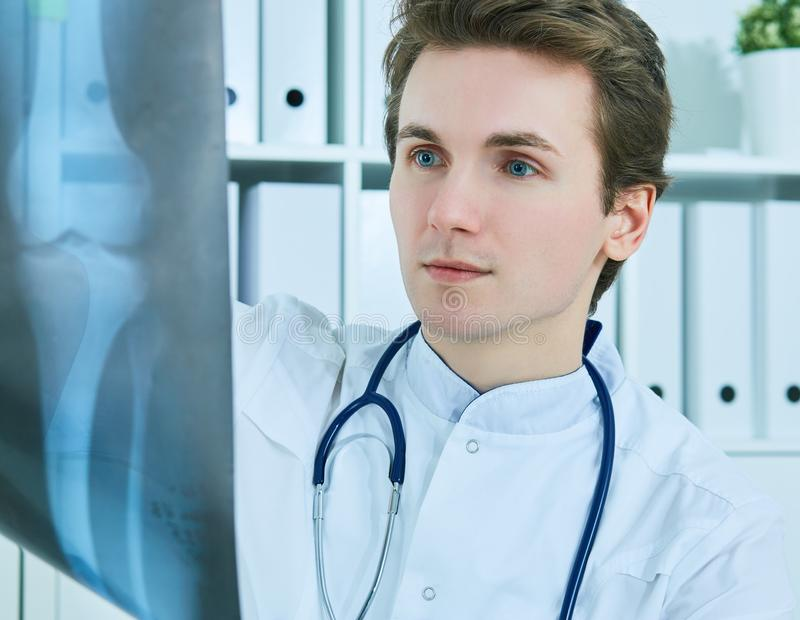 Feche acima do retrato do doutor masculino novo que guarda a imagem do raio X ou do roentgen foto de stock royalty free