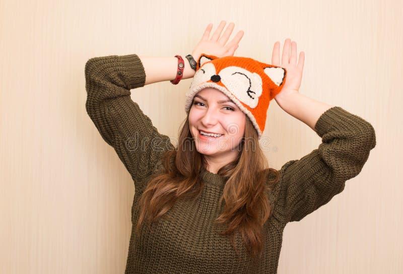 Feche acima do retrato do estúdio da menina alegre do moderno na raposa engraçada h imagens de stock