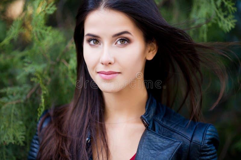 Feche acima do retrato exterior da mulher moreno bonita nova com olhos verdes e cabelo saudável longo fotos de stock