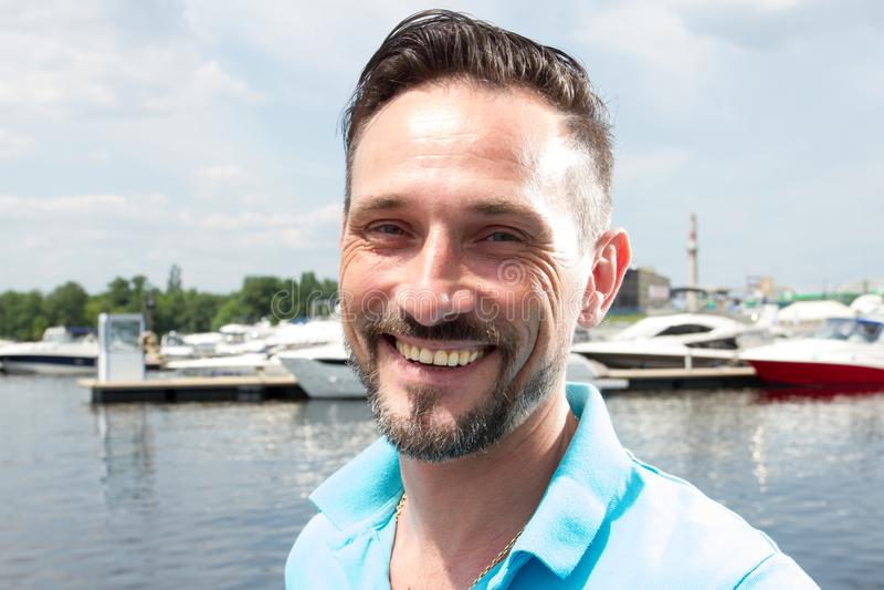 Feche acima do retrato do homem desportivo considerável que sorri e que olha na câmera contra um lago com barcos Close-up de um s foto de stock royalty free
