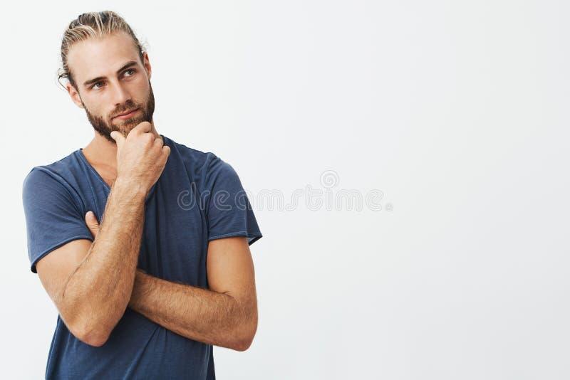 Feche acima do retrato do homem farpado bonito com penteado à moda e a roupa que olham de lado e que pensam sobre a sala imagem de stock