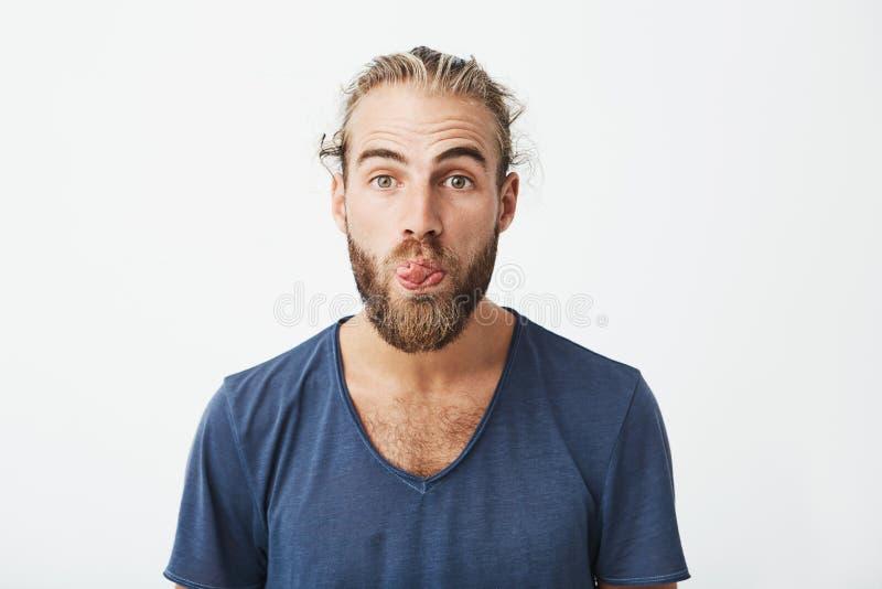 Feche acima do retrato do indivíduo engraçado atrativo com penteado à moda e da barba que mostra a língua e que faz a expressão p imagens de stock royalty free