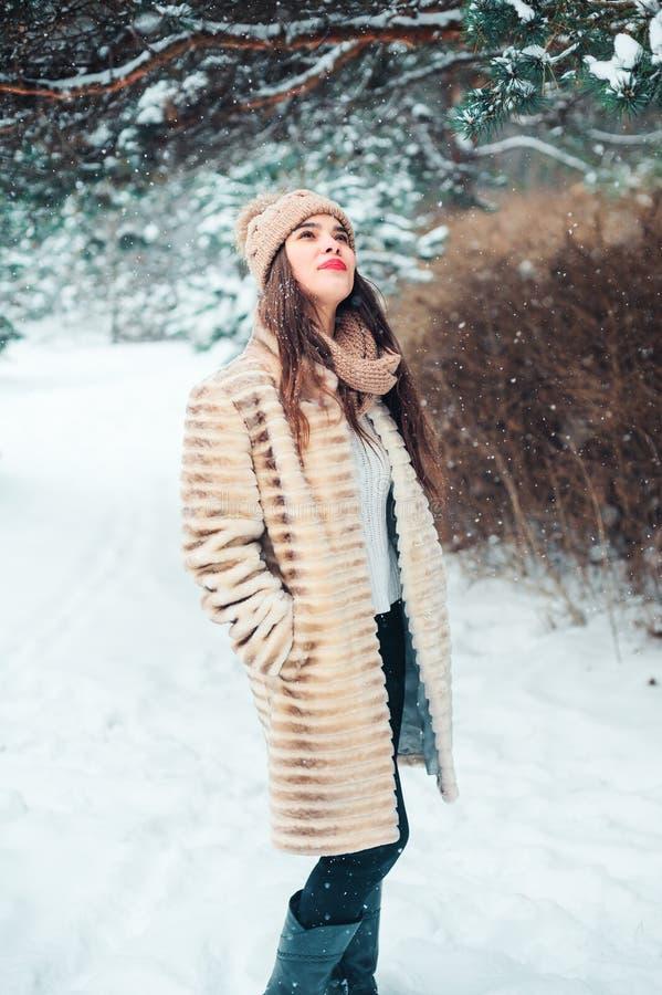 feche acima do retrato do inverno da jovem mulher de sorriso que anda na floresta nevado imagens de stock