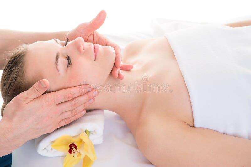 Feche acima do retrato principal da jovem mulher que tem a massagem facial em s fotografia de stock