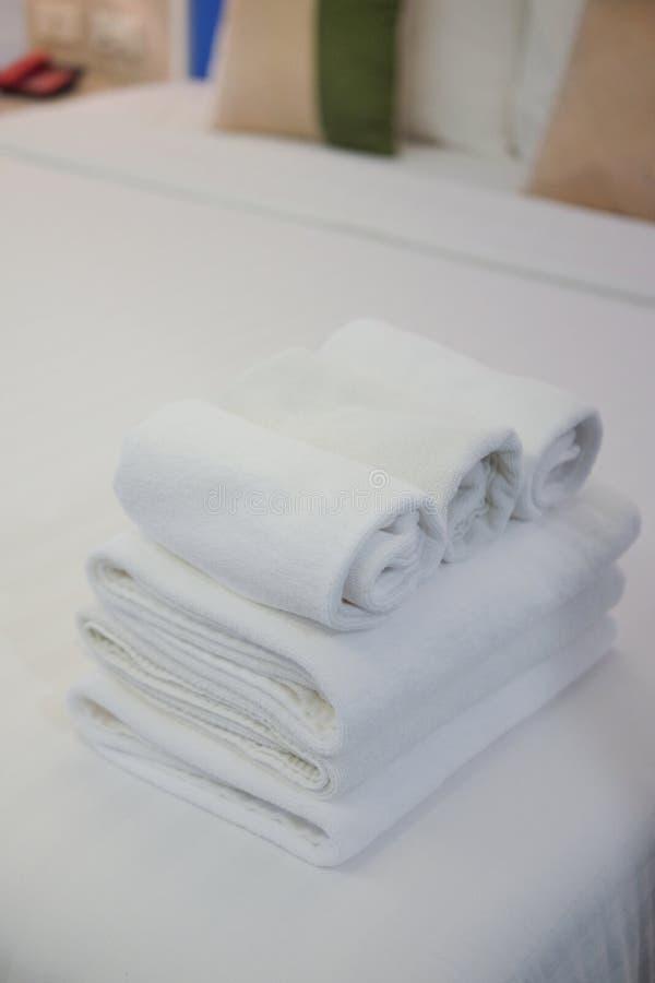Feche acima do rolo da toalha branca na cama imagem de stock