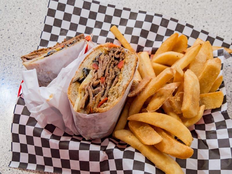 Feche acima do sanduíche de bife da Tri ponta com batatas fritas imagem de stock