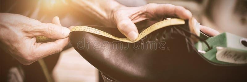Feche acima do sapateiro que mede uma sapata fotos de stock royalty free