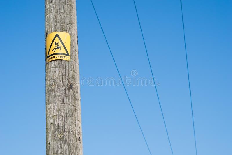 Feche acima do sinal do perigo no pólo da eletricidade fotos de stock royalty free