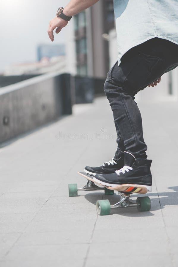 Feche acima do skater& x27; pés de s na equitação do longboard na rua dentro fora imagens de stock royalty free