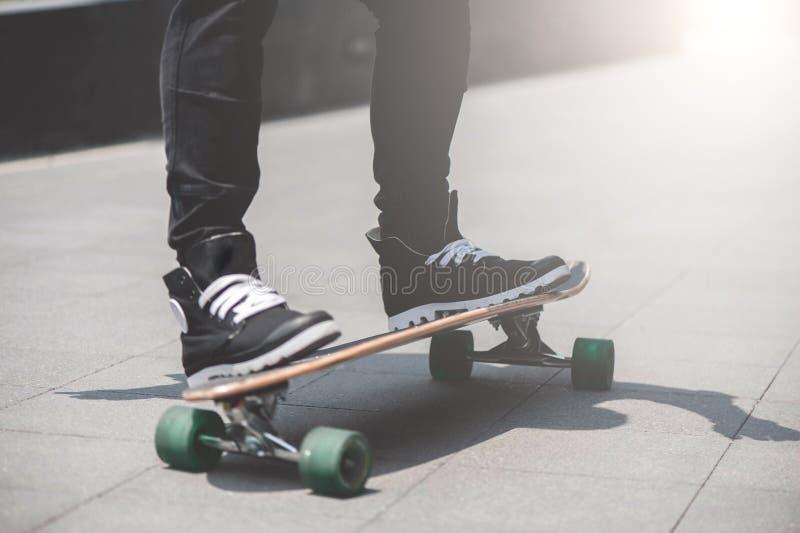 Feche acima do skater& x27; pés de s na equitação do longboard na rua dentro fora fotos de stock