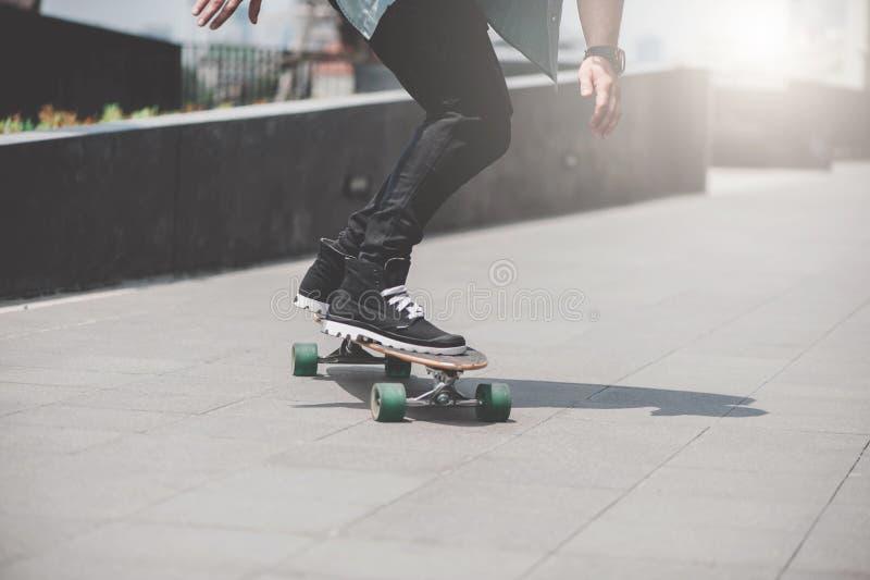 Feche acima do skater& x27; pés de s na equitação do longboard na rua dentro fora foto de stock